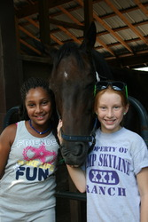 Equestrian campers caring for the horses